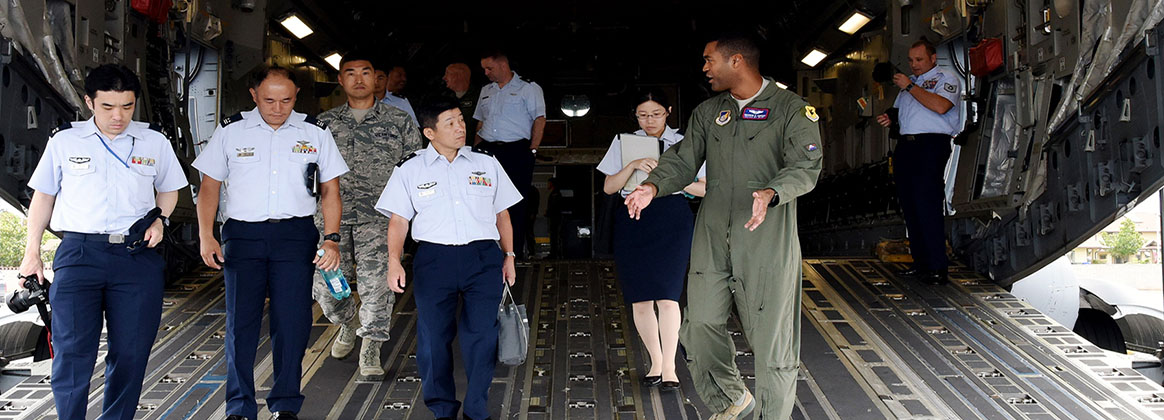 JOINT BASE PEARL HARBOR-HICKAM, Hawaii (July 11, 2018) - U.S. Air Force Capt. Warren Carter, Operations Element Chief, 18th Aeromedical Evacuation Squadron, Det 1, speaks with Koukuu Jieitai, Japan Air Self Defense Force, Maj. Gen. Shinya Bekku, Koku Jieitai Surgeon General aboard a C-17 Globemaster III at Joint Base Pearl Harbor-Hickam.  During Bekku's visit, he met with U.S. Air Force Col. (Dr.) Lee Harvis, Pacific Air Forces Command Surgeon to discuss future bi-lateral medical partnership opportunities.