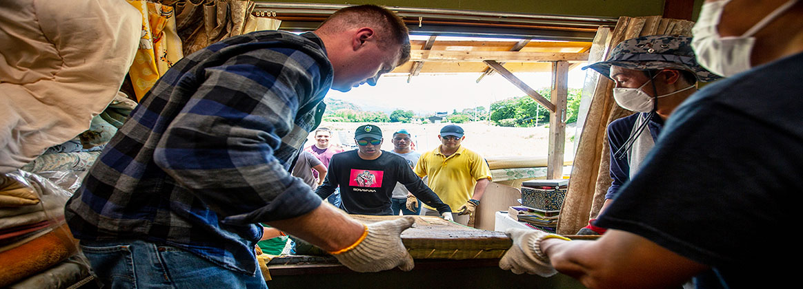 MCAS IWAKUNI, YAMAGUCHI, Japan (July 13, 2018) - U.S. Marines and Sailors clean out damaged household items from a home during a volunteer event in Shuto Town, Iwakuni City.  The volunteer event, organized by the Marine Corps Community Services Single Marine Program, provided service members with the opportunity to help local Japanese residents clean up and recover after the area was flooded by excessive rainfall.