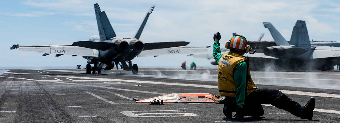 PHILIPPINE SEA (July 13, 2018) - Aviation Boatswain's Mate (Equipment) 2nd Class Alfred Ranili, from Cebu City, Philippines, signals for the launch of an F/A-18E Super Hornet, assigned to Strike Fighter Squadron (VFA) 115, on the flight deck of the Navy's forward-deployed aircraft carrier, USS Ronald Reagan (CVN 76). Ronald Reagan, the flagship of Carrier Strike Group 5, provides a combat-ready force that protects and defends the collective maritime interests of its allies and partners in the Indo-Pacific region.