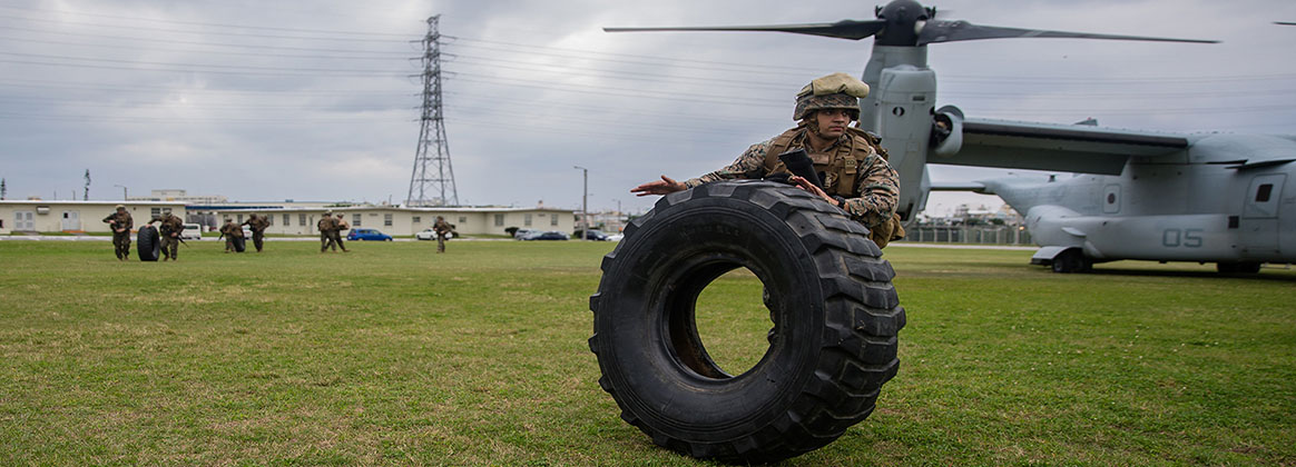 CAMP HANSEN, OKINAWA, Japan (Jan. 14, 2019) - Lance Cpl. David S. Gutierrez rolls a Medium Tactical Vehicle Replacement tire during helicopter support team training at Camp Foster, Okinawa, Japan. Landing Support Company, 3rd Transportation Support Battalion, Combat Logistics Regiment 3, 3rd Marine Logistics Group supported Marine Medium Tiltrotor Squadron 265, Marine Aircraft Group 36, 1st Marine Aircraft Wing during external lift training, which ensures pilots and landing support specialists are able to communicate and transport gear from one location to another. Gutierrez, a landing support specialist, is a native of El Paso, Texas.