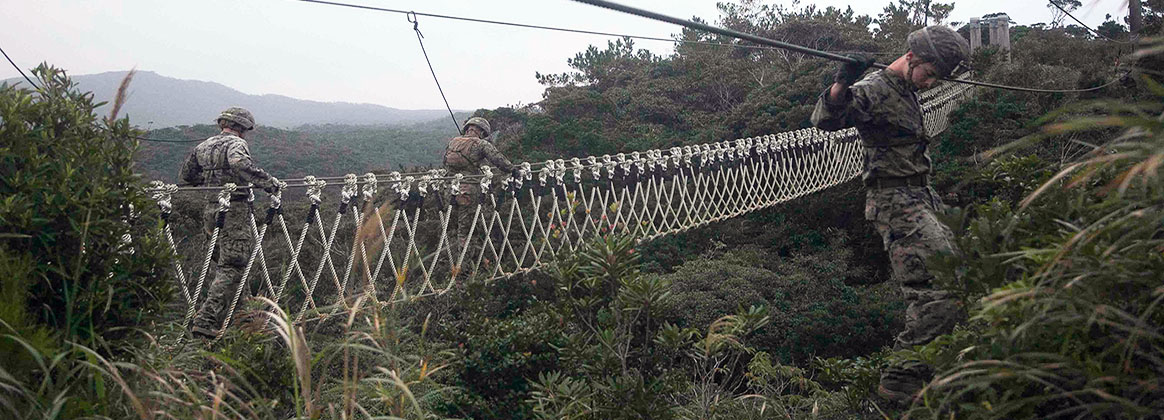 OKINAWA, Japan (Jan. 16, 2018) - U.S. Marines with the 3rd Battalion, 2nd Marine Regiment, currently assigned to 3rd Marine Division, cross the two- and three-strand bridges at the beginning of the endurance course at the Jungle Warfare Training Center (JWTC) on Okinawa, Japan. The Marines and Sailors are at JWTC to compete in the squad competition.