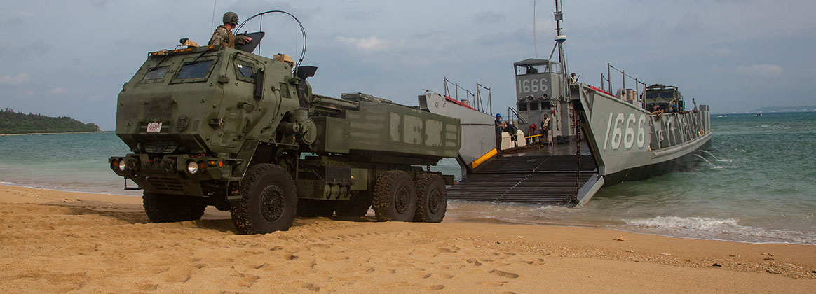 KIN BLUE, OKINAWA, Japan (Aug. 14, 2019) - A landing craft, utility assigned to the amphibious transport dock ship USS Green Bay (LPD 20), lowers its ramp to unload a High Mobility Artillery Rocket System from 3rd Battalion, 12th Marine Regiment, 3rd Marine Division, as part of a simulated amphibious raid, at Kin Blue, Okinawa, Japan, Aug. 14, 2019. This simulated amphibious raid marks the first time that HIMARS have been inserted by landing craft, utility, demonstrating the Marine Air-Ground Task Force's ability to conduct combined-arms maneuver from amphibious shipping.