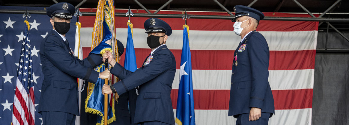MISAWAI AIR BASE, Japan (July 13, 2020) - U.S. Air Force Lt. Gen. Kevin B. Schneider, U.S. Forces Japan and 5th Air Force commander, left, passes the wing guidon to Col. Jesse J. Friedel, 35th Fighter Wing commander, during an official change of command ceremony at Misawa Air Base, Japan, July 13, 2020. The passing of the guidon symbolizes the relinquishment of command from the outgoing commander to the incoming commander. Friedel comes to Misawa from Osan Air Base, Republic of Korea, where he served as the 51st Fighter Wing vice commander.