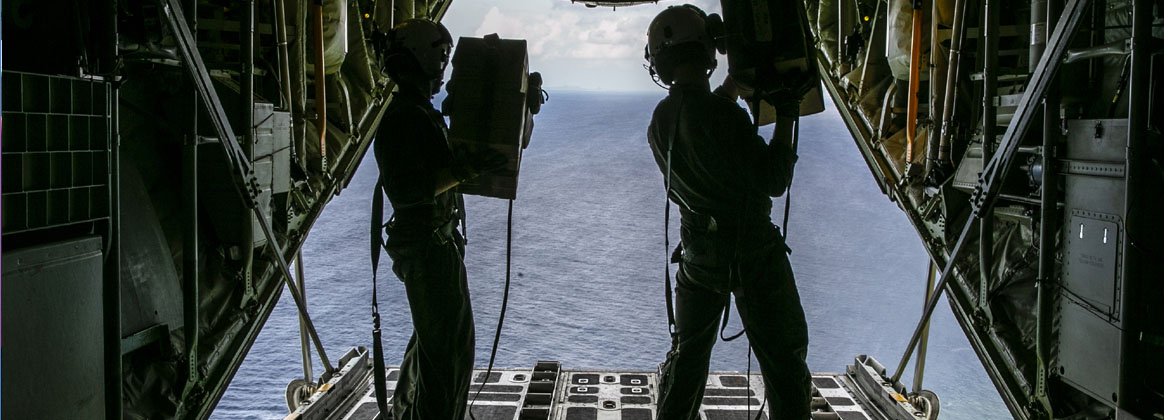 IE SHIMA, OKINAWA, Japan (Sept.15, 2021) - U.S. Marine Corps Sgt. Louis Martin, left, and Cpl. Montana Bingen, both fixed-wing aircraft crew masters with Marine Aerial Refueler Transport 152, Marine Aircraft Group 12, 1st Marine Air Wing, prepare to manually deploy cargo rigged with a parachute from the back of a C-130 aircraft during an air delivery exercise over Ie Shima island, Okinawa, Japan, Sept. 15, 2021. Marines with VMGR-152, and 3d Landing Support Battalion, Combat Logistics Regiment 3, 3d Marine Logistics Group, conducted the air delivery of blood and medical supplies, and conducted static line and free fall jumps over Ie Shima island.