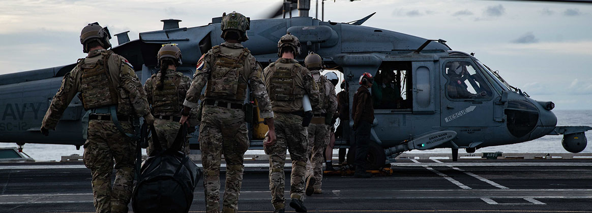 """INDIAN OCEAN (Sept. 19, 2021) - Sailors assigned to Explosive Ordnance Disposal Mobile Unit (EODMU) 5, attached to Commander, Task Force (CTF) 70, board an MH-60S Seahawk, attached to the """"Golden Falcons"""" of Helicopter Sea Combat Squadron (HSC) 12, to conduct fast-rope evolutions on the flight deck of the Navy's only forward-deployed aircraft carrier USS Ronald Reagan (CVN 76). Ronald Reagan, the flagship of Carrier Strike Group 5, provides a combat-ready force that protects and defends the United States, and supports alliances, partnerships and collective maritime interests in the Indo-Pacific region."""