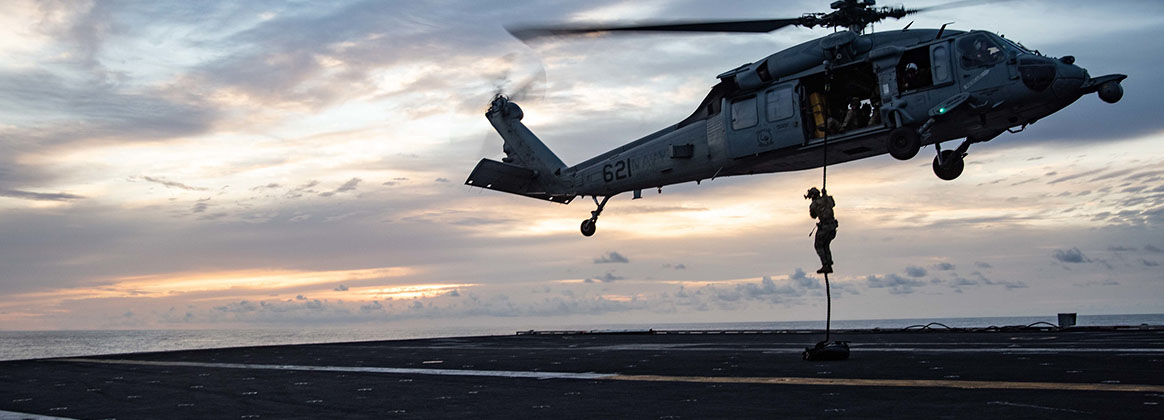 """INDIAN OCEAN (Sept. 19, 2021) - Sailors assigned to Explosive Ordnance Disposal Mobile Unit (EODMU) 5, attached to Commander, Task Force (CTF) 70, conduct a fast-rope evolution from an MH-60S Seahawk, attached to the """"Golden Falcons"""" of Helicopter Sea Combat Squadron (HSC) 12, on the flight deck of the Navy's only forward-deployed aircraft carrier USS Ronald Reagan (CVN 76). Ronald Reagan, the flagship of Carrier Strike Group 5, provides a combat-ready force that protects and defends the United States, and supports alliances, partnerships and collective maritime interests in the Indo-Pacific region."""