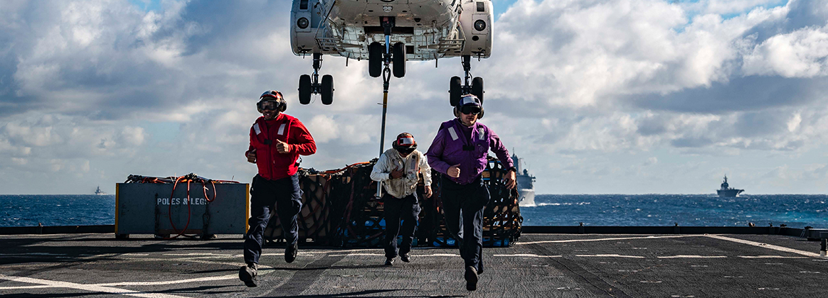 CORAL SEA (June 25, 2019) Personnel Specialist Seaman Dedrick Johnson, left, from Vidalia, Georgia, Boatswain's Mate 1st Class Jacob Meadows, center, from Lake Elsinore, California, and Machinist Mate 3rd Class Tyler Martin, from Perrin, Texas, run past the foul line as a SA-330J Puma picks up pallets from the flight deck of the amphibious dock landing ship USS Ashland (LSD 48) prior to a replenishment-at-sea (RAS) with the amphibious assault ship USS Wasp (LHD 1) and fleet replenishment oiler USNS Rappahannock (T-AO 204). Ashland, part of the Wasp Amphibious Ready Group, with embarked 31st Marine Expeditionary Unit (MEU), is operating in the Indo-Pacific region to enhance interoperability with partners and serve as a ready-response force for any type of contingency, while simultaneously providing a flexible and lethal crisis response force ready to perform a wide range of military operations. 190625-N-WI365-1075